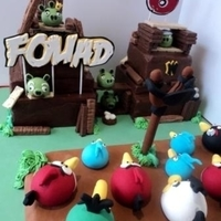 Angry Birds This was made for my son's birthday. Birds made with fondant. I used chocolate bars for the planks, etc. Cake was pretty big and was...