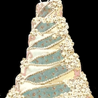 Teal And Champagne Wedding Cake Tiered round wedding cake with square base, base crackled fondant two toned with cobblestone embossed appliques. Gum paste roses, entire...