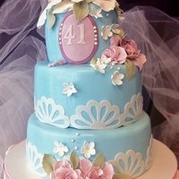Pink And Blue Birthday Cake Fondant covered three tiered cake with gum paste flowers