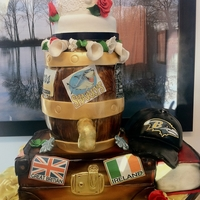 Themed Wedding Cake Vintage suitcase with travel stickers as base. Wooden keg with symbolic stickers of couples memories. Top is a mini wedding cake. To the...