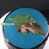 Yoda Chocolate ganache covered cake with cookies and cream filling. Yoda is made of fondant and modeling chocolate