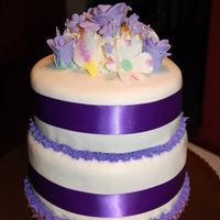 Purple Flowers Hand made fondant.. Hand made flowers... Lemon botton layer.. french vanilla with bavarian cream filling top layer