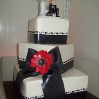 Black And White Ball Of Chain Square vanilla cake with whipped cream filling and frosting w/fondant bottom ribbona and fondant bow, w/a red gumpaste flower and above the...