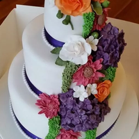 Cadburys Purple Round Wedding Cake Flower bouquet. roses, orange, purple, geranium,