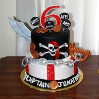 Captain Jonathan Pirate themed cake with gumpaste sword, number, gold coins, chain, and jolly roger