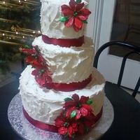 Christmas Wedding Cake   textured buttercream with red satin ribbon and gumpaste poinsettias