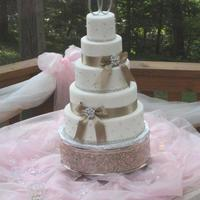 Glam Wedding Cake   Wedding cake complete with rhinestone trim and beautiful broaches that match bridesmaids broaches on dresses.