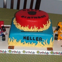 Transformers Birthday Vanilla cake with Fondant accents and toys on on the cake board.