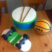 Favorite Things Cake! The drum was made of stacked cakes. The skateboard is RKT, and the basketball is a Styrofoam ball covered in fondant then pressed with a...