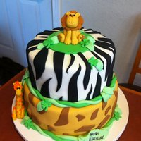 Jungle Cake!! The characters are made from fondant. The child was born on St. Patrick's day.... hence the shamrocks :)
