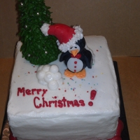"A Penguin Christmas Made for The Houston Zoo. A 6"" two layer vanilla cake covered in white buttercream. The Christmas Tree is a sugar cone covered in..."