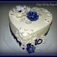 "Blue And Silver Anniversary This is a 9"" heart shaped cake frosted in buttercream and decorated with gumpaste flowers and molded decorations using the Wilton..."