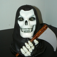 "Grim Reaper I used the Wilton 3D pan for the head and an 8"" round cake underneath. The robes are Satin Ice fondant, and I used mmf for the rest of..."