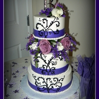 Purple And Black Wedding Cake I made this cake for a good friend of mine. It's frosted in buttercream with a fondant ribbon and fresh flowers.