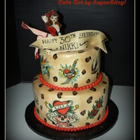 Pinup Tattoo Cake This cake was covered in fondant and hand painted with food color gels. The banner and pinup girl is made of fondant and hand painted.