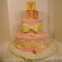 Baby Shower In Pink And Yellow Cake covered in MMF, block are wilton candy melts in a mold, pacifier and everything else is MMF, hand made. They loved it. cake is...