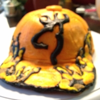 Hunting Cap Camo Cake  chocolate hunting cap with chocolate buttercream and white camo cake with tinted buttercream camo. Hat brim, deer logo, and sign post are...