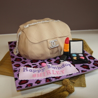 Chanel Bag Cake A chocolate cake shaped into a bag covered in fondant. Accessories and board covered in gumpaste.