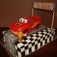 "Lightning Mcqueen Cake   Chocolate with choc bc. Track is 11x15x5"". Car is carved cake both covered in fondant. Finish line and Piston cup made from gp."