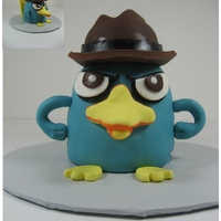 Perry The Platypus   A cake for my daughter who loves Perry, PandF. He's 5 inch rounds carved at the top with an rkt hat.