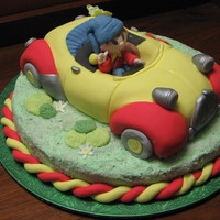 Noddy In Car Noddy built from vanilla cake,covered with fondant and placed on another vanilla cake.