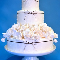 White Wedding Cake   3 tier round wedding cake with a 4th tier of sugar flowers, roses and tulips.