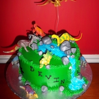 Dinosaur Cake   Covered in buttercream, rocks are fondant, water is piping gel, and dinosaurs are toys.