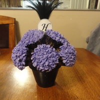 Purple Cupcake Bouquet   This cupcake bouquet was used as a centerpiece at a bridal shower. The H and feather are not edible!