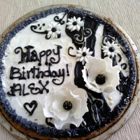 Cookie Cake Big chocolate chip cookie cake decorated with black swirls and fondant flowers