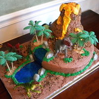 Dinosuar Birthday This is bithday cake for my 3 yr old grandson. He is all about dinosaurs right now. Cake is wasc/chocolate bc. Volcano is rkt. Trees, rocks...
