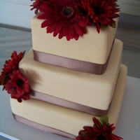 Autumn Love A beautiful autumn wedding cake. Covered in champagne colored fondant with latte colored ribbon border and claret colored Gerbera and...