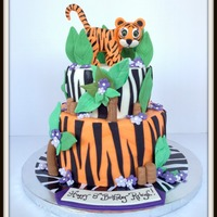 Tiger Cake Tiger is made from gumpaste. Design was originally made up by the birthday girl. She wanted a tiger, purple flowers and an orange cake. I...