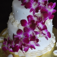 Fresh Orchid Beach Cake Covered with fondant, and decorated with fresh orchids and fondant shells made with a mold.