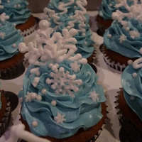 Winter Wonderland Cupcakes Buttercream swirls, poinsettias, and trees. Snowflakes and tree outlines are royal icing.