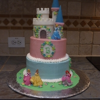 Disney Princess Castle Cake For a Cinderella-themed birthday party. Buttercream tiers with fondant castle, flowers, and plaque. Leaves, grass, and monogram are royal...