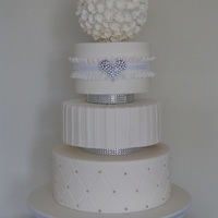 White Wedding With Bling 10/8/6 inch cakes seperated with bling spacers and topped with large hydrangea flower ball. TFL