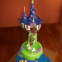 Rapunzel's Tower  Tower is RKT covered in fondant and modeling chocolate. Details in Royal Icing. Base is Vanilla Cake/Vanilla BC covered in MMF - fondant...