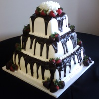 Tuxedo Wedding Cake With Strawberries The tiers are covered in fondant and poured ganache. Accents of chocolate covered strawberries at the base & on the sides. Topper is a...