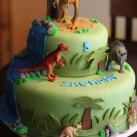 Dinosaur Plastic dinos atop a fondant covered cake with piping gel waterfall