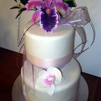 Exquisite Orchids Two tier cake with sugar flowers, the top orchid is a Cattleya Maxima, filler flowers are Pandorea Jasminoides with buds and leaves and...