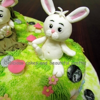 Bunny Rabbits Cake  A cake done for a 1 year old baby's birthday.All the four rabbits,the tree log,mushrooms,stones,flowers are all made with fondant.This...