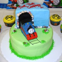 Thomas The Train   Thomas the Train covered in marshmallow fondant . The rocks were chocolate rocks and toy train .