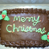 Merry Christmas Yellow cake with chocolate buttercream and holly leafs.