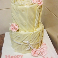 White Chocolate Birthday Cake A 2 tier white chocolate mud cake filled with raspberry butter cream and decorated with white chocolate panels and sugar roses.