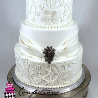 Faux Lace Buttercream with fondant accents. Brooch purchased by the bride. TFL!