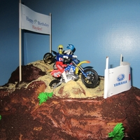 Dirt Bike Motorx Cake This is a triple chocolate cake covered in fondant, chocolate icing and cookie crumbs.