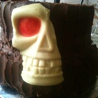 Halloween Cake Chocolate biscuit cake on bottom, chocolate fudge on top, filled and covered with ganache, with a white skull decoration