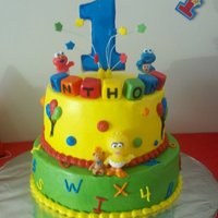Sesame Street A Sesame Street cake for a child's first birthday. Vanilla and chocolate cake, iced in buttercream. The blocks and stars are fondant,...