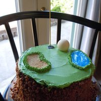 Golf Cake Chocolate Toffee cake with buttercream topping. Golf balls are made from a mold with white chocolate.
