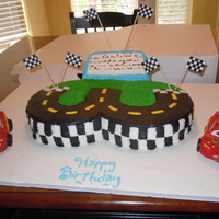 Pixar Cars Cake cars are molded from white chocolate and decorated with fondant. Cake is covered in buttercream frosting.